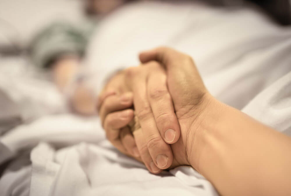 Closeup of Holding Hands in Hospital Bed